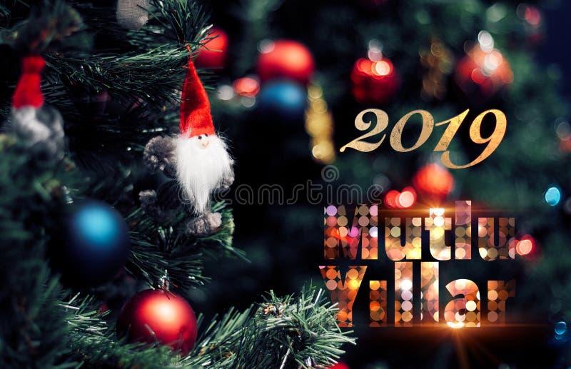 Nahaufnahme des roten Flitters hängend von einer verzierten Kiefer mit Text 2019 Mutlu Yillar bedeutet guten Rutsch ins Neue Jahr stockbild