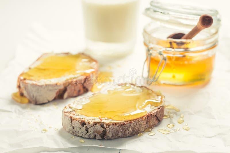 Nahaufnahme des Sandwiches mit Honig mit Milch zum Frühstück stockbild