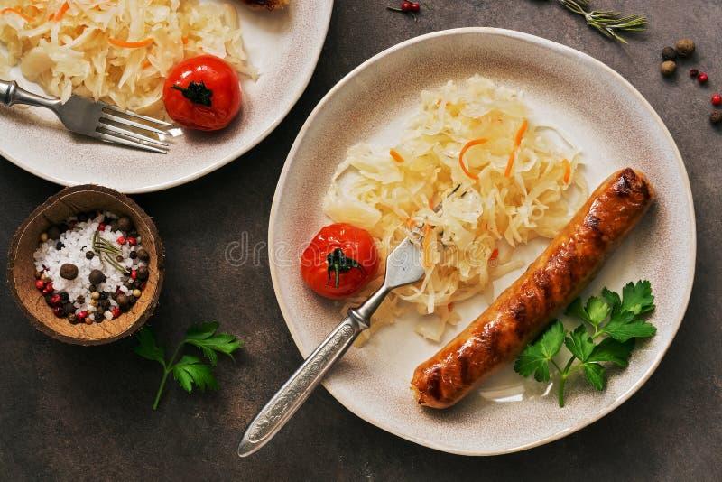 Nahaufnahme des Sauerkrauts mit gebratener Wurst auf einem dunklen rustikalen Hintergrund Obenliegende Ansicht, flache Lage stockfoto