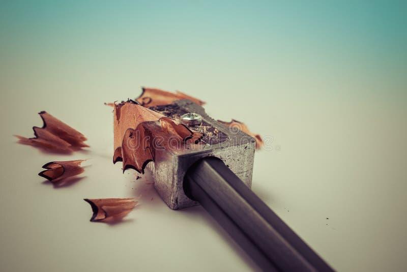 Nahaufnahme des Schärfens eines Bleistifts mit einem grauen Metallbleistiftspitzer mit hölzernen Schnitzeln - Konzept der Schulbi stockfoto