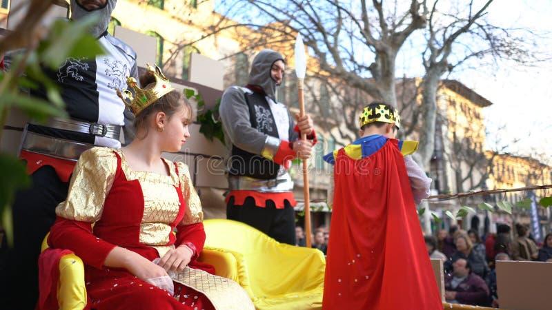 Nahaufnahme des schönen jungen Mädchens im Königinkostüm, das auf dem Thron nahe zwei Rittern und Jungen im Umhang und in der Kro lizenzfreies stockbild