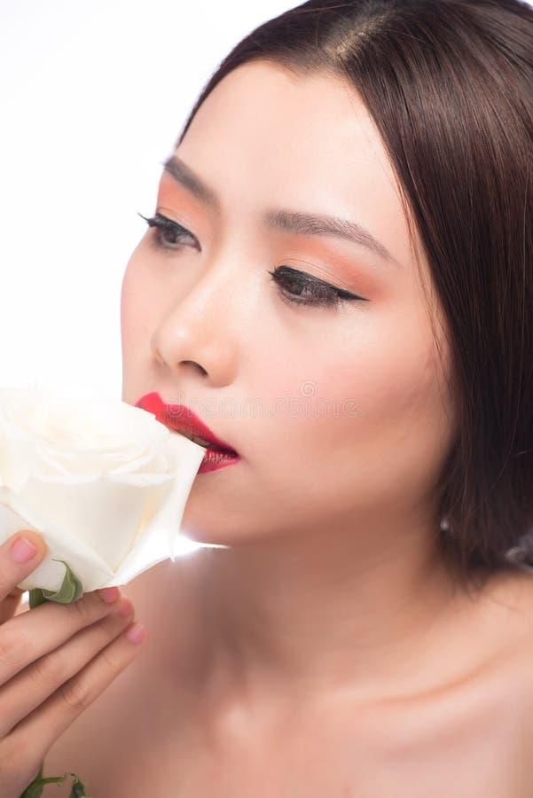 Nahaufnahme des schönen Mädchens mit rosafarbener Blume des Weiß lizenzfreies stockfoto