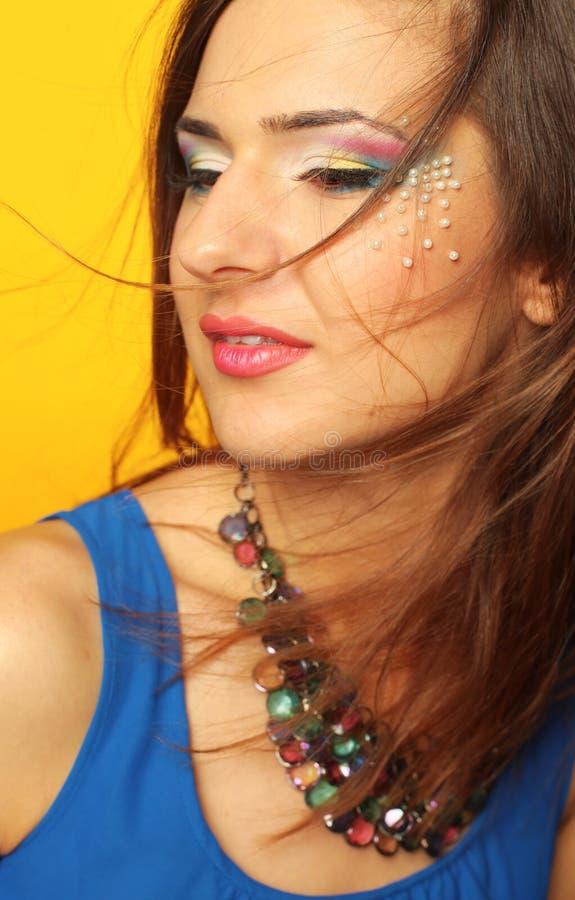 Nahaufnahme des schönen weiblichen Gesichtes mit buntem Make-up und der Lippen, die Schmuck und windiges Haar tragen stockfotografie