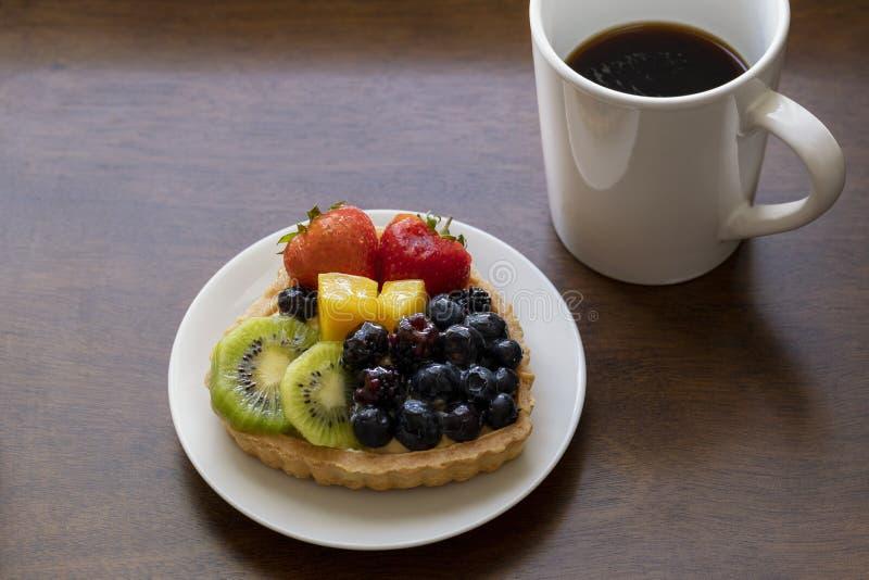 Nahaufnahme des scharfen Nachtischs der Frucht mit Erdbeeren, Kiwi, Käsecreme und heißem schwarzem Kaffee lizenzfreie stockfotos