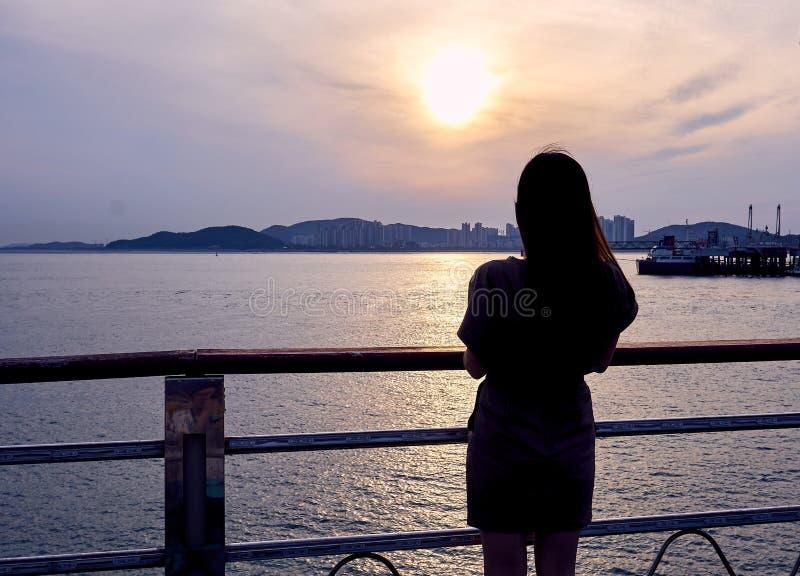 Nahaufnahme des Schattenbildes einer asiatischen Frau, welche die Sonnenuntergangansicht von Incheon, Südkorea betrachtet lizenzfreie stockfotos