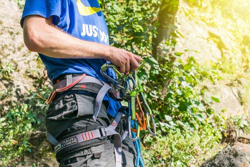 Nahaufnahme des Schenkelbergsteigers mit Ausrüstung auf Gurt, Stände nahe Felsen lizenzfreies stockbild