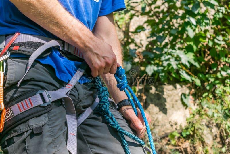 Nahaufnahme des Schenkelbergsteigers mit Ausrüstung auf Gurt, Stände nahe Felsen lizenzfreies stockfoto