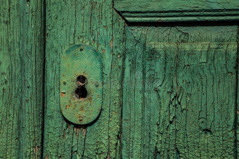 Nahaufnahme des Schmiedeeisenschlüssellochs in einer alten hölzernen abgenutzten Tür lizenzfreie stockfotos