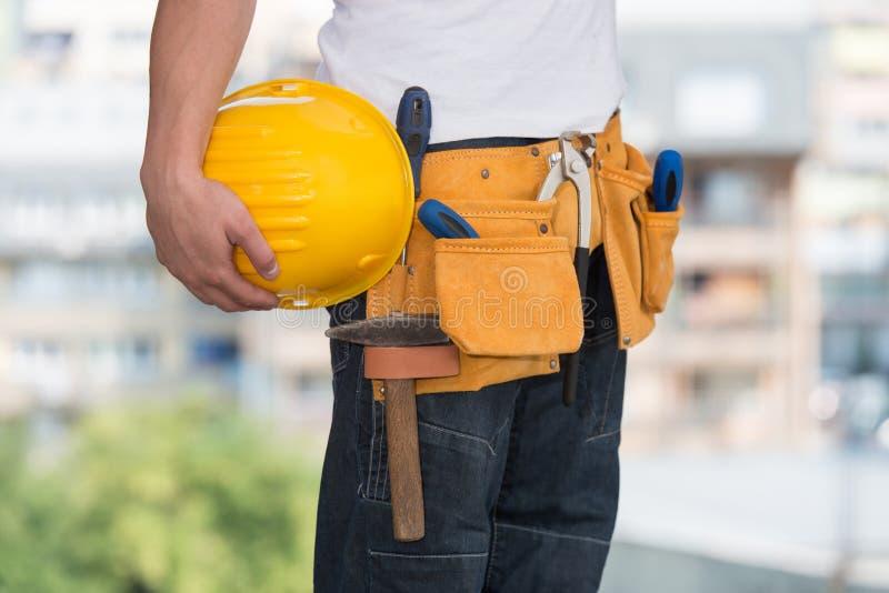 Nahaufnahme des Schutzhelms halten durch Bauarbeiter stockbild