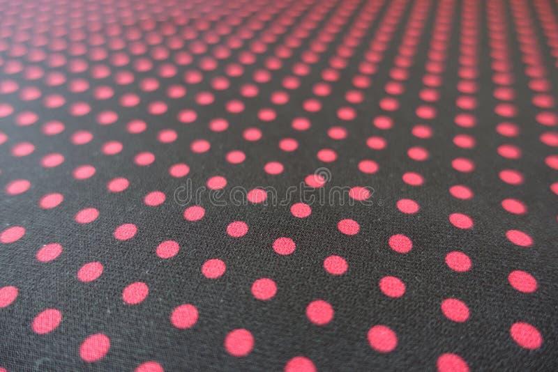 Nahaufnahme des schwarzen Gewebes mit roten Punkten drucken stockfotografie