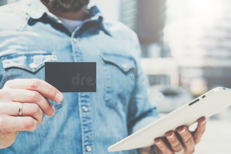 Nahaufnahme des schwarzen leeren Kredites, des Geschäfts, in der Hand des jungen Geschäftsmannes nennen, der Visitenkarte und der stockfotografie