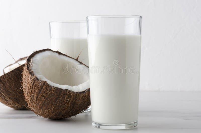 Nahaufnahme des selbst gemachten Milchkefirs, Hälfte der Kokosnuss auf sauberer Marmortabelle stockbilder