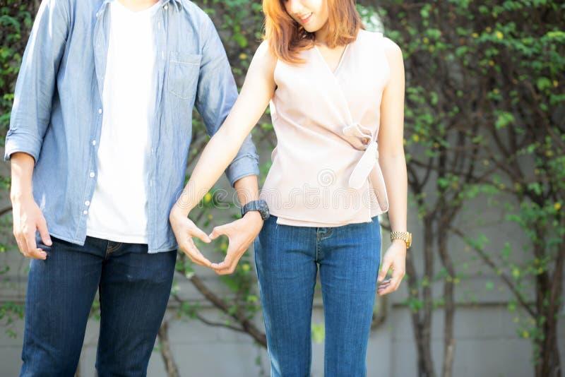 Nahaufnahme des Spa?es des gl?cklichen Paars Gestenherzform mit der Hand im Freien zusammen machend lizenzfreie stockbilder