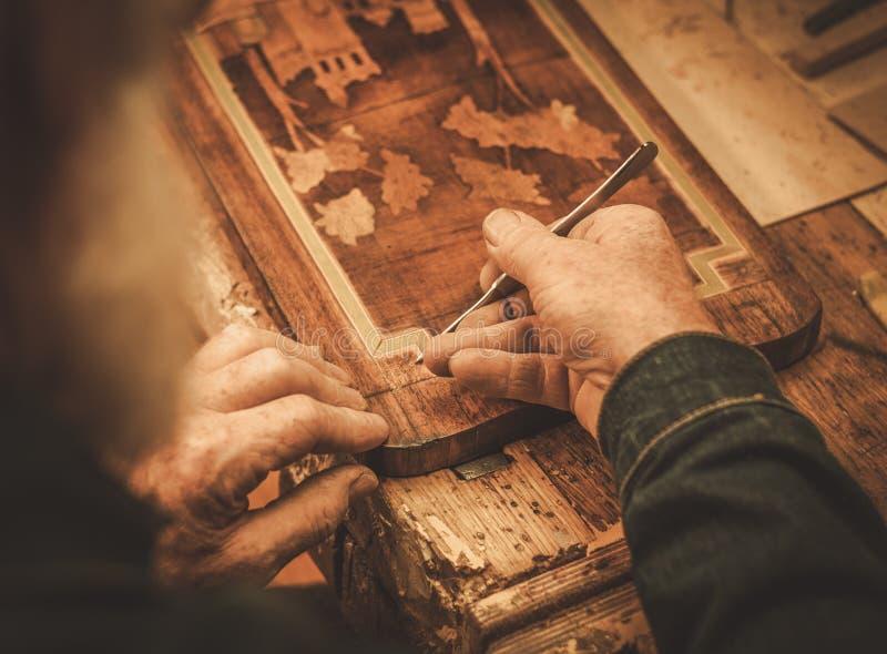 Nahaufnahme des Stärkungsmittels übergibt das Arbeiten mit antikem Dekorelement in seiner Werkstatt stockbilder