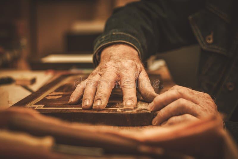 Nahaufnahme des Stärkungsmittels übergibt das Arbeiten mit antikem Dekorelement in seiner Werkstatt lizenzfreie stockfotografie