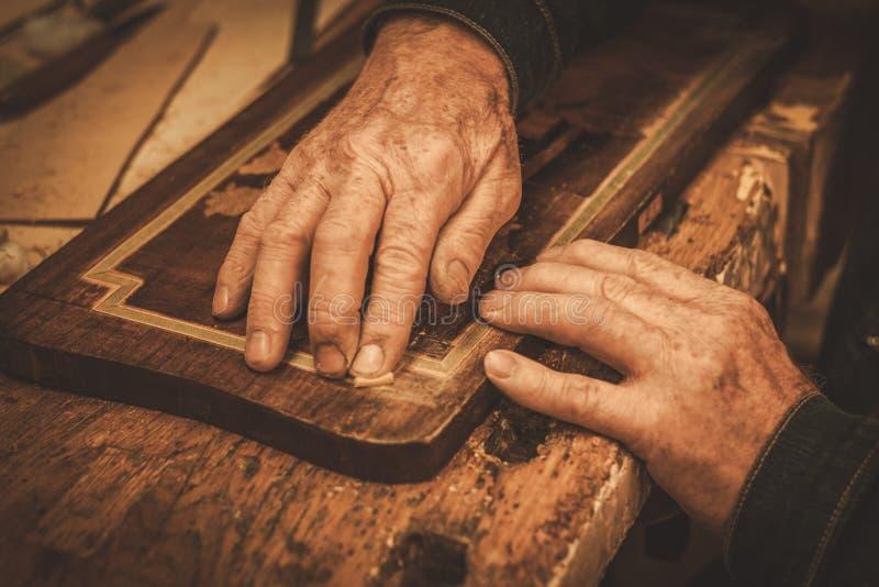 Nahaufnahme des Stärkungsmittels übergibt das Arbeiten mit antikem Dekorelement in seiner Werkstatt stockfotografie