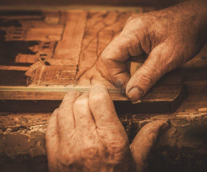 Nahaufnahme des Stärkungsmittels übergibt das Arbeiten mit antikem Dekorelement in seiner Werkstatt stockfoto