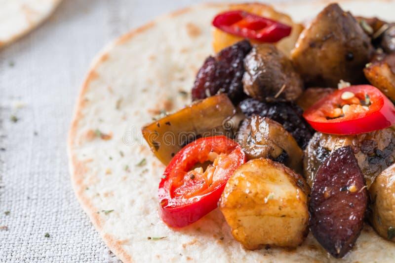 Nahaufnahme des Tacos mit gegrillten Pilzen, spanische würzige Wurstchorizo, mexikanische Tortillas, zypriotisches Käse halloumi, stockfoto