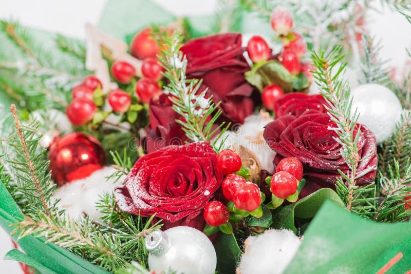 Nahaufnahme des Weihnachtsblumenstraußes mit Blumen und der Fichte mit Schnee stockfotos