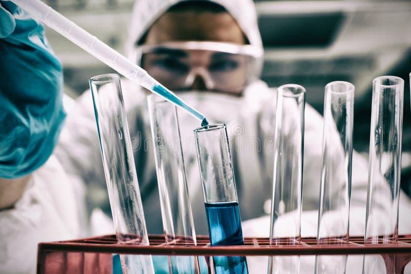 Nahaufnahme des Wissenschaftsstudenten blaue Flüssigkeit im Reagenzglas fallenlassend lizenzfreies stockbild