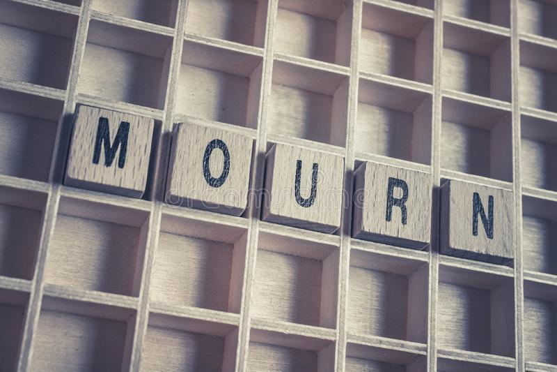 Nahaufnahme des Wortes beklagen gebildet durch Holzklötze auf einem Bretterboden lizenzfreie stockfotografie