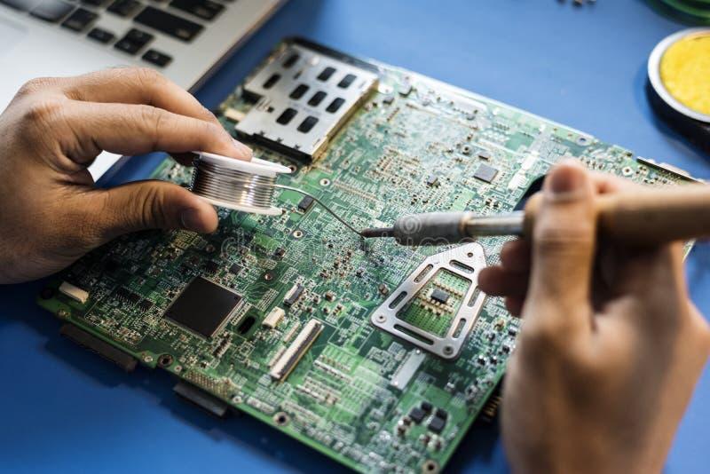 Nahaufnahme des Zinns lötend mit ElektronikLeiterplatte stockfoto
