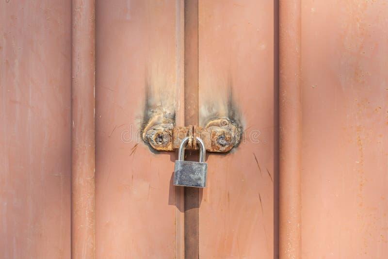 Nahaufnahme, die das Metallvorhängeschloß auf altem rostigem Metalleingang doo sich befestigen stockfotografie