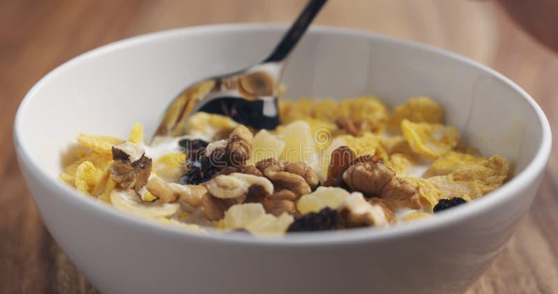 Nahaufnahme, die mit einem Löffelfrühstück mit Corn Flakes und Mischung von Nüssen und von Früchten isst stockfoto