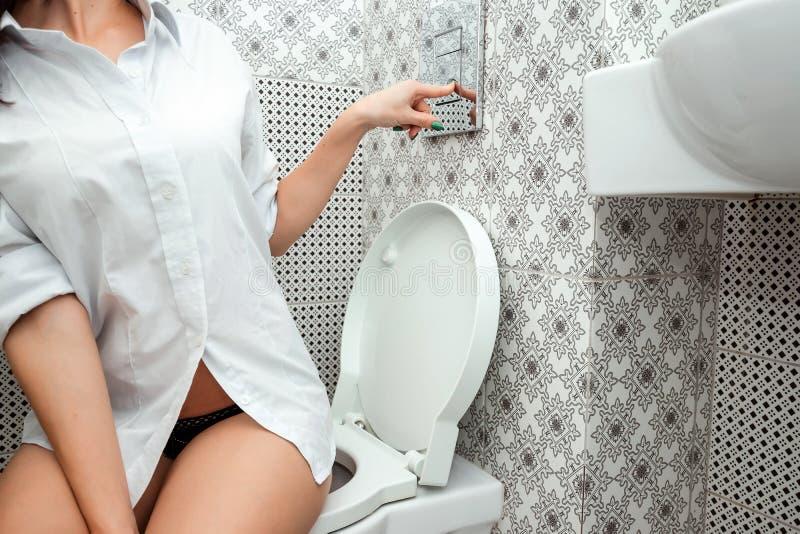 Nahaufnahme, eine Ente, die auf der Toilette sitzt, drückt den ebenen Knopf Das Konzept von intestinalen Problemen, Diarrhöe, H lizenzfreie stockfotografie