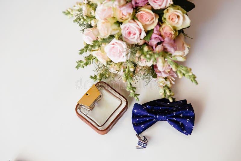 Nahaufnahme eine Fliege, Parfüm, Manschettenknöpfe und ein Hochzeitsblumenstrauß auf einer weißen Tabelle Bekleidungszubehör für  lizenzfreies stockfoto