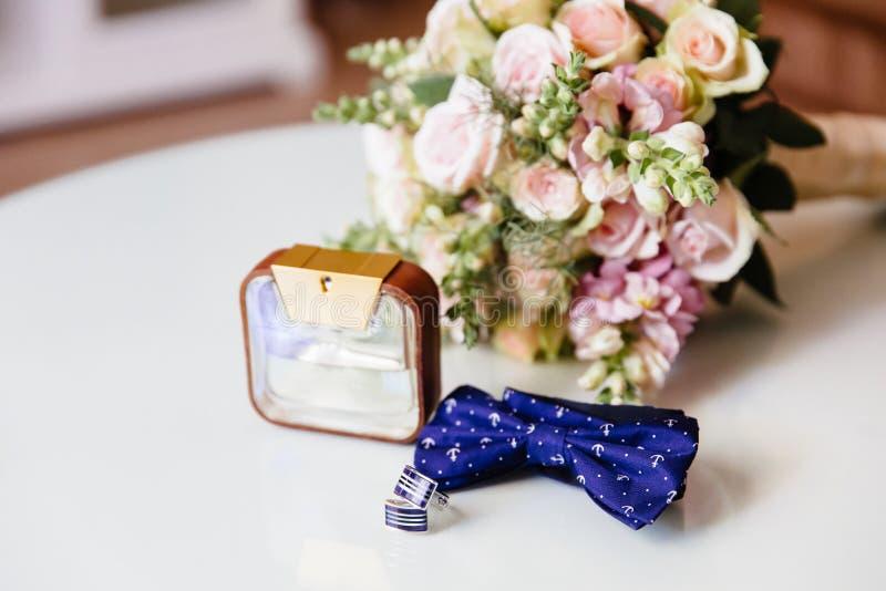 Nahaufnahme eine Fliege, Parfüm, Manschettenknöpfe und ein Hochzeitsblumenstrauß auf einer weißen Tabelle Bekleidungszubehör für  lizenzfreie stockfotos