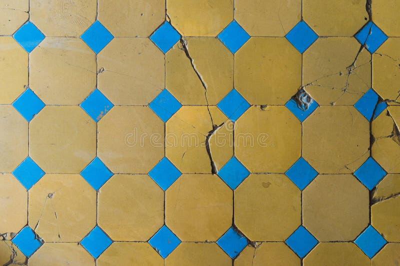 Nahaufnahme einer alten Bodenfliese mit einem zweifarbigen Muster Rissige Bodenfliesen stockbilder