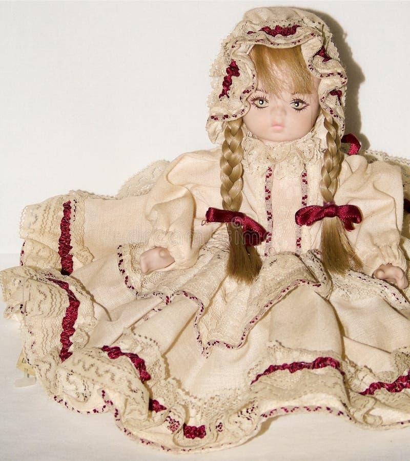 Nahaufnahme einer blonden Porzellanpuppe, die auf weißem Hintergrund lokalisiert wird, Weinlese spielt lizenzfreies stockfoto