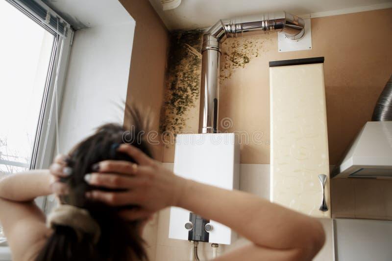 Nahaufnahme einer entsetzten Frau, die Form auf Wand betrachtet stockfoto