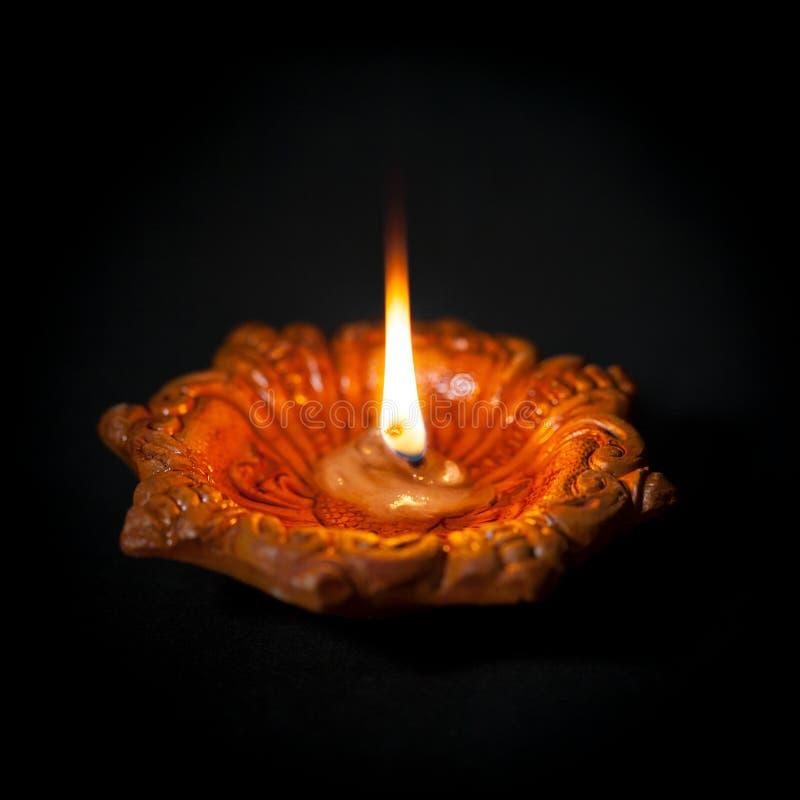 Nahaufnahme einer erklärenden tönernen Öl-Lampe oder des Diya auf dunklem Hintergrund stockbild