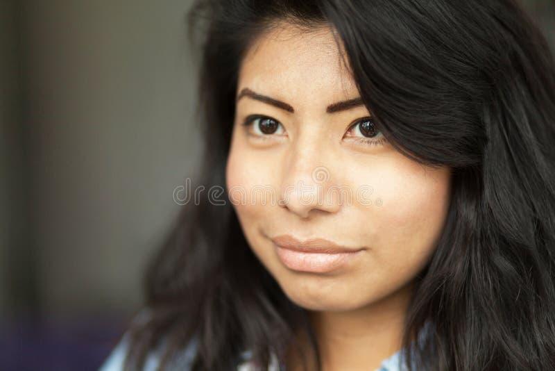 Nahaufnahme einer ernsten jungen Spanierin, die weg schaut Sie ist lokalisiert auf Grau trauriges stockfotografie