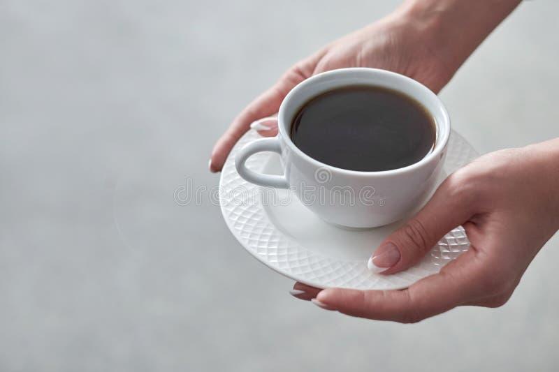 Nahaufnahme einer Frau ` s Hand, die eine Schale heißen Kaffee im Büro hält stockbild