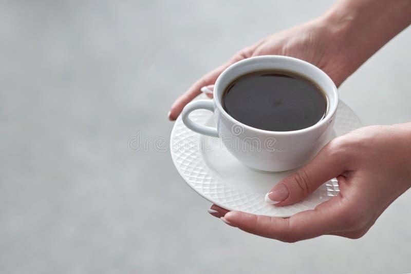 Nahaufnahme einer Frau ` s Hand, die eine Schale heißen Kaffee im Büro hält stockfoto