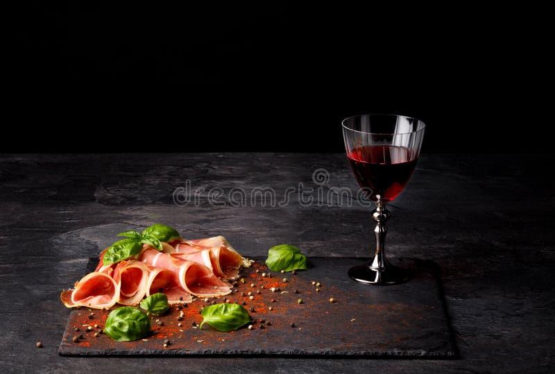 Nahaufnahme einer Gastronomiezusammensetzung Ein volles Weinglas, ein Prosciutto und Basilikumblätter auf einem schwarzen Hinterg stockfoto