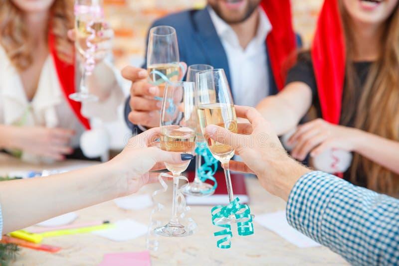 Nahaufnahme einer Gruppe Freunde, die mit Champagner auf einem festlichen Hintergrund zujubeln Weihnachtsereigniskonzept stockfotos