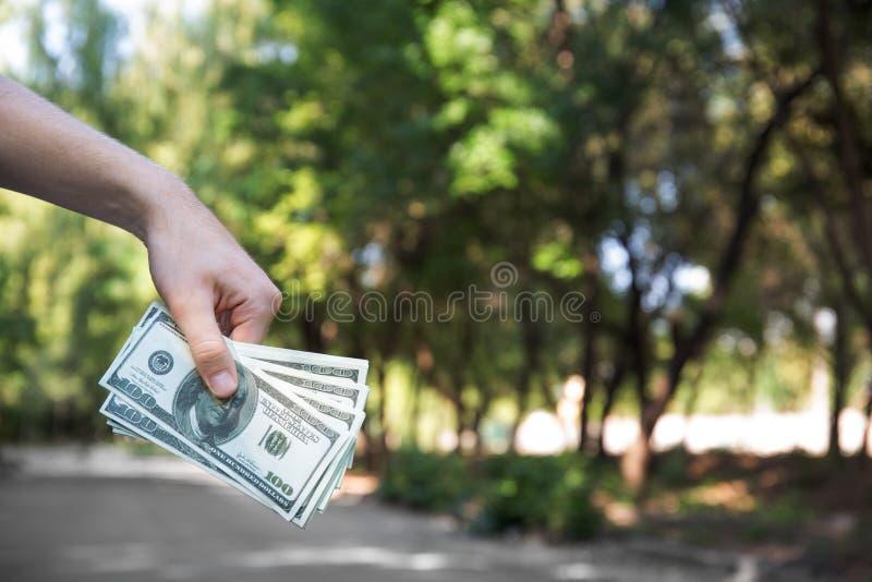 Nahaufnahme einer Hand mit amerikanischen Dollar Bemannen Sie das Halten des Papiergeldes auf einem unscharfen natürlichen Hinter lizenzfreies stockfoto
