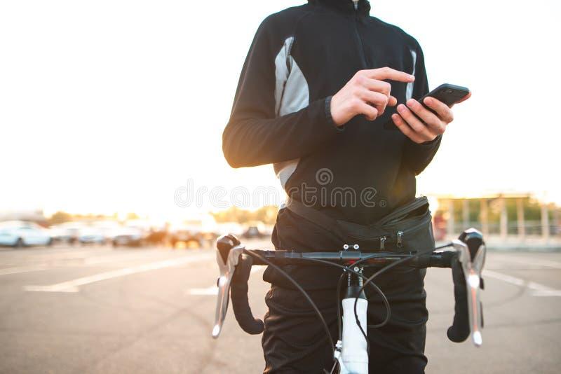 Nahaufnahme einer Hand mit einem Smartphone in einem Mann mit einem Fahrrad Fahrradreiterrest und Anwendung eines Smartphone stockbilder