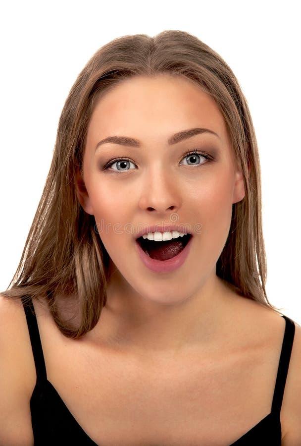 Nahaufnahme einer jungen Frau, die gegen weißen Hintergrund aufgeregt schaut lizenzfreies stockbild