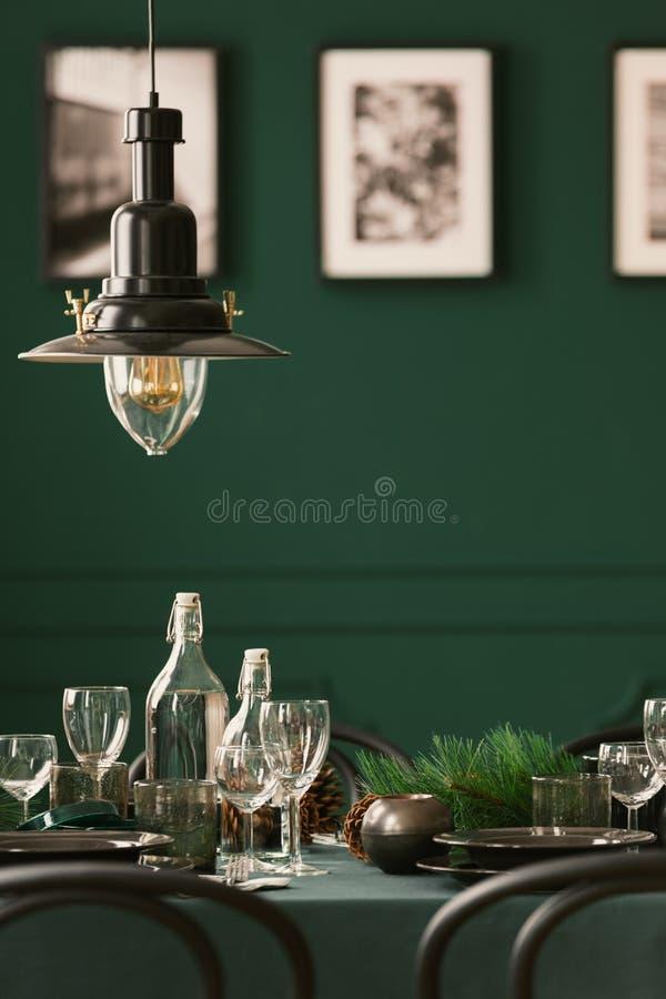 Nahaufnahme einer Metalllampe, die über einer eleganten Tabelle mit grünem Stoff hängt Unscharfe Wand mit Fotos im Hintergrund Re stockbilder