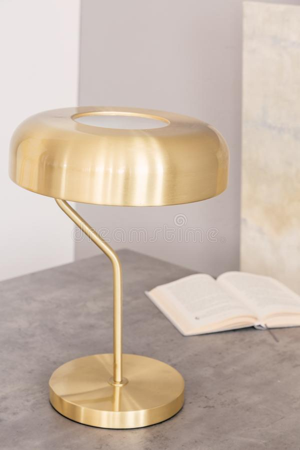 Nahaufnahme einer minimalen stilvollen Goldfarbschreibtischlampe und des offenen Buches auf einer Tabelle in einem Büroinnenraum  stockbilder