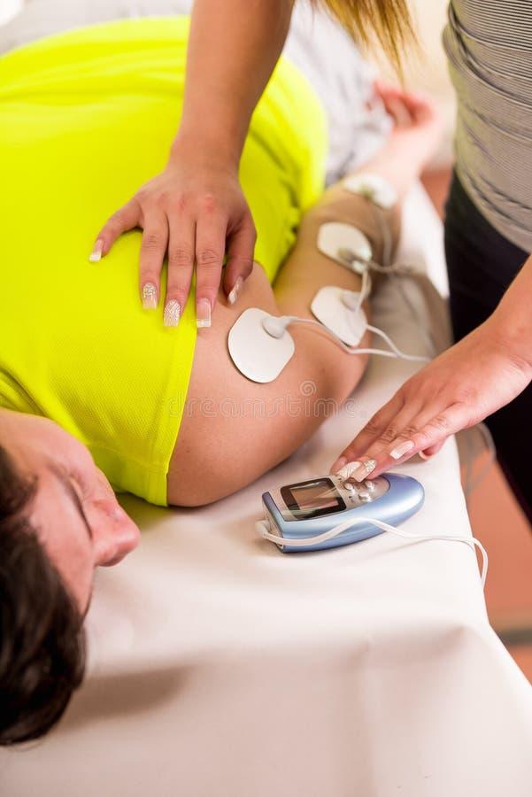 Nahaufnahme einer persönlichen Trainerhand, die ein electrostimulator Elektroden in den Arm eines männlichen deportist trägt a ei stockfotos