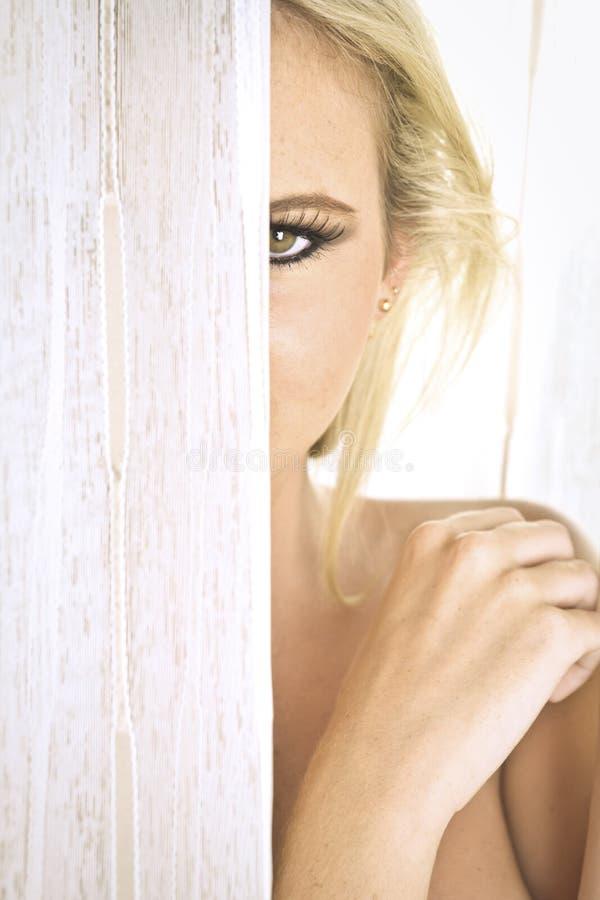 Nahaufnahme einer schulterfreien Blondine, die hinter einem Vorhang sich versteckt stockfoto