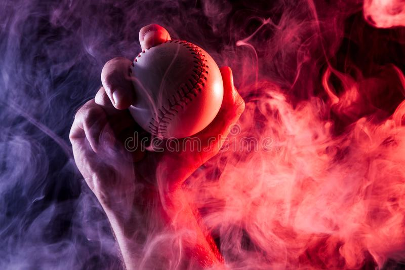 Nahaufnahme einer starken männlichen Hand, die einen weißen Baseballball hält lizenzfreie stockfotografie