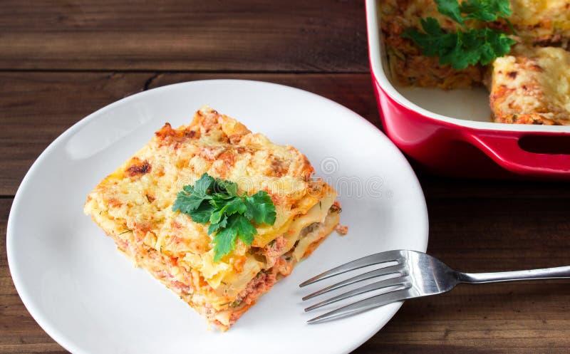 Nahaufnahme einer traditionellen Lasagne, die mit parskey Blättern überstiegen wurde, diente auf einer weißen Platte mit Gabel stockfoto