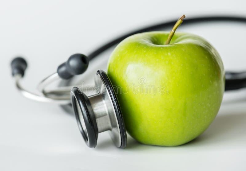 Nahaufnahme eines Apfels und des gesunden Lebensmittels des Stethoskops und des Gesundheitskonzeptes lizenzfreie stockfotos